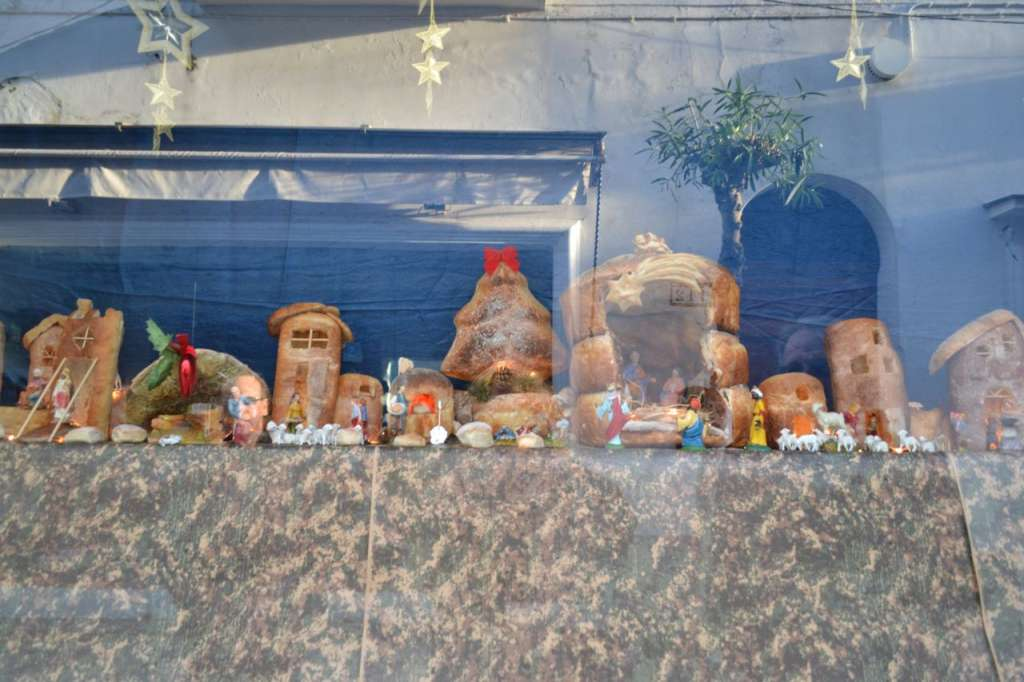 A presepe made of bread in a bakery window.